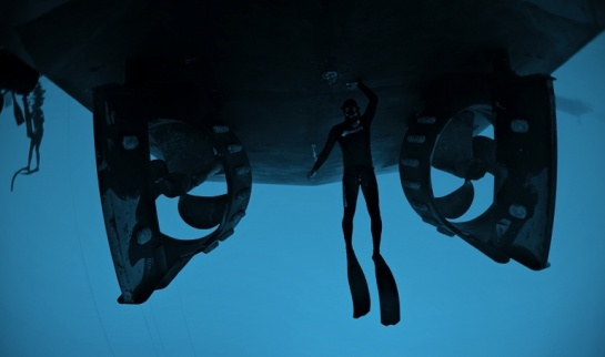 Free diver under the hull of EDT Niovi while anchored
